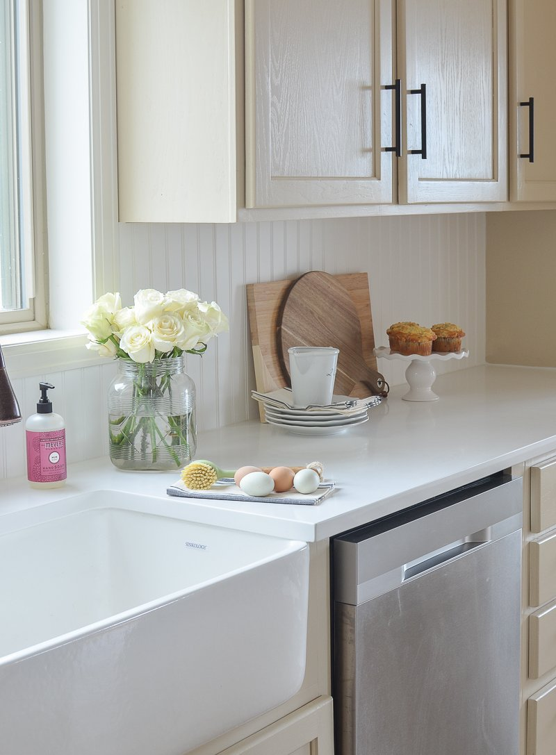 Farmhouse style kitchen makeover with white quartz countertops and farmhouse sink.