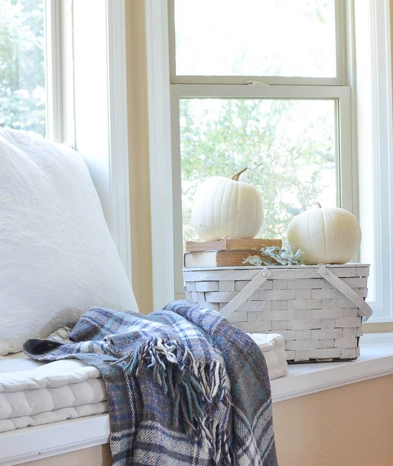 farmhouse style fall decor in the front room. White pumpkins on old picnic basket.