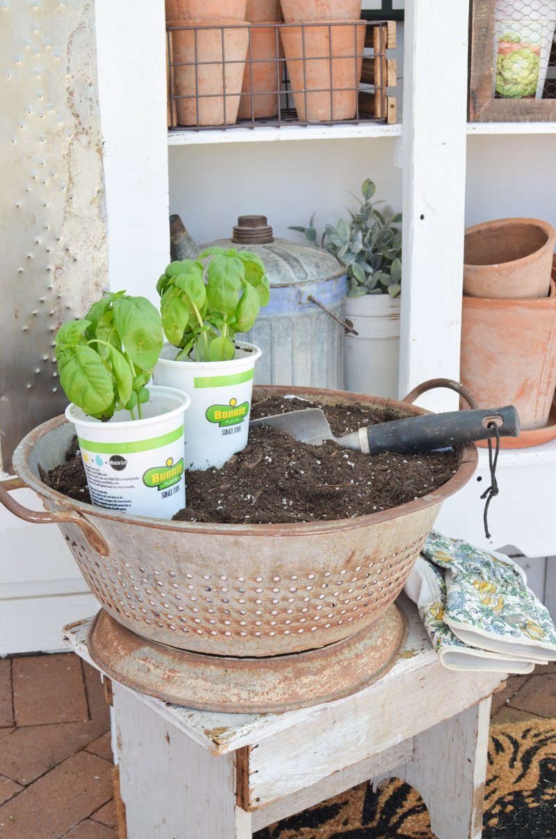 Outdoor Farmhouse Style Garden Storage Cabinet. Vintage colander used to hold potting soil!