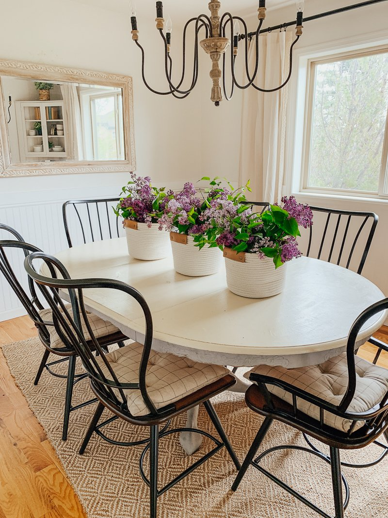 Simple summer centerpiece with fresh lilacs and woven baskets. Easy farmhouse inspired decor idea!