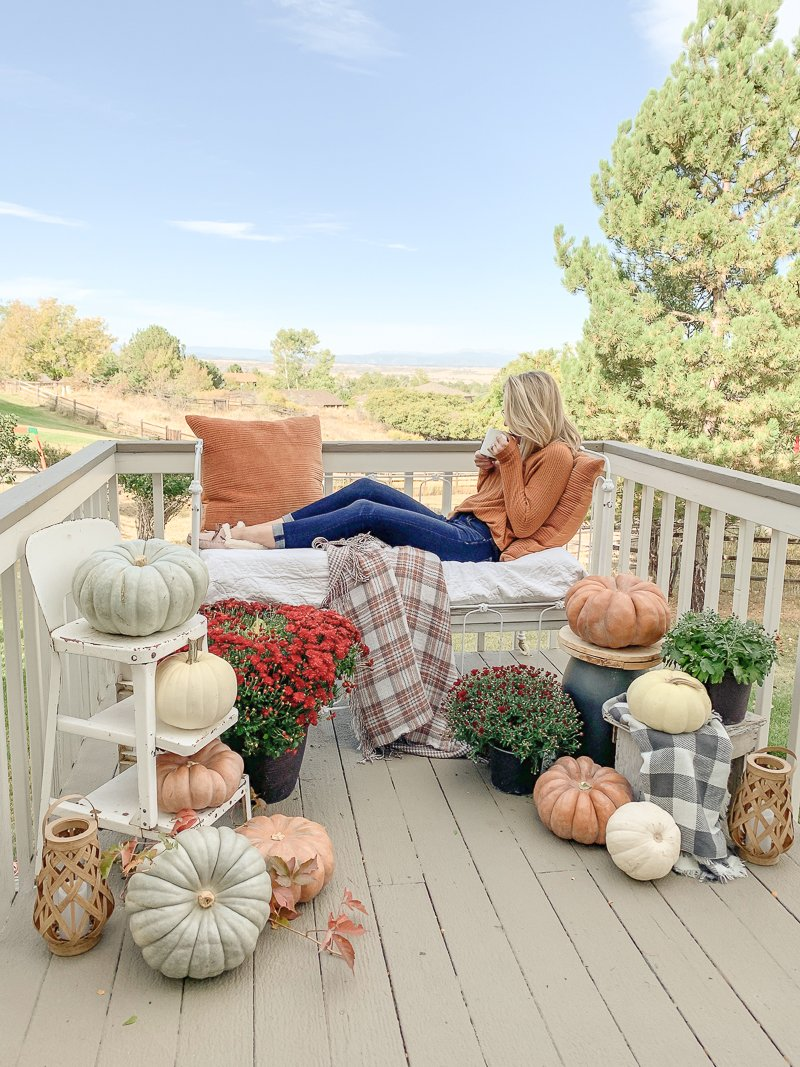 Cozy fall patio. Farmhouse style fall decor ideas with pumpkins, mums, and cozy fall blankets.